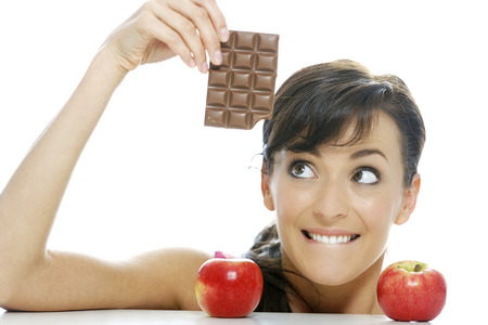 guilty pleasures: Young woman torn between a chocolate bar and fresh apple