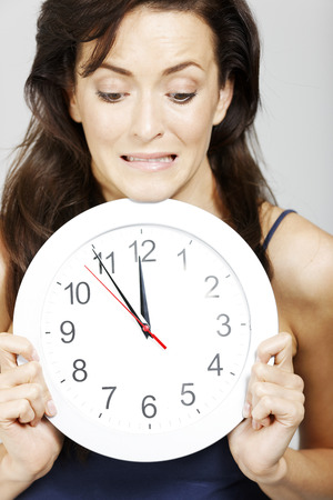 Young woman holding clock face expressing anticipation