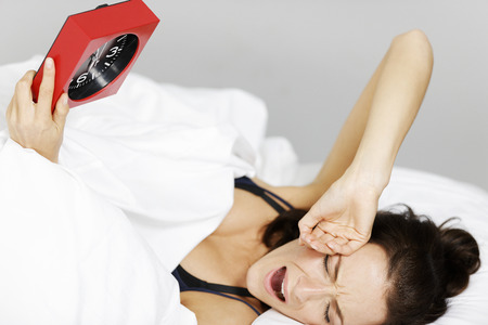 woken: Young woman being woken up by her alarm clock Stock Photo