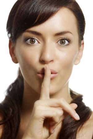 Woman holding a finger over her lips to shush someone.
