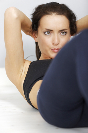 situp: Young woman doing a sit-up on the floor.