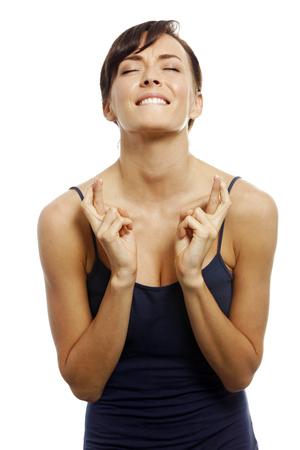 Jonge vrouw met gekruiste vingers kijkt hoopvol