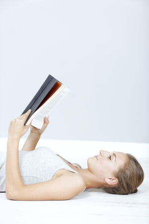 Beautiful young woman lying on the floor reading a hardback book photo