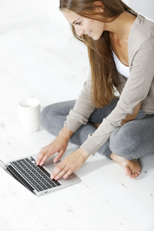 Beautiful young woman working from home on her floor using a laptop photo