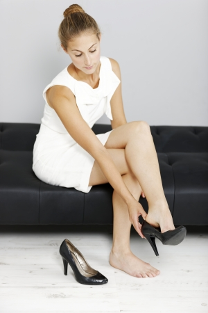 off day: Beautiful young business woman taking her shoes off after a long day.