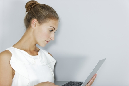 Attractive young business woman holding a laptop photo