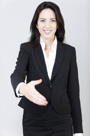 Professional business woman in a smart suit extending her hand out. photo
