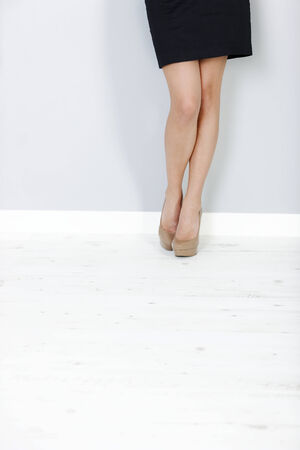Attractive young womans legs against a wall photo
