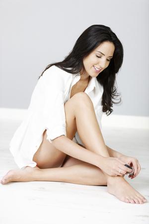 Beautiful young woman in open white shirt varnishing her nails photo