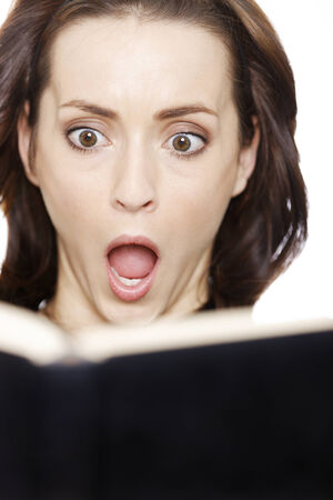 gasp: Woman expressing shock whilst ready from a book isolated on white background. Stock Photo