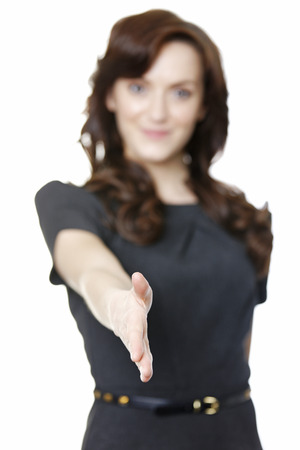 Attractive business woman holding her hand out expressing a greeting gesture photo
