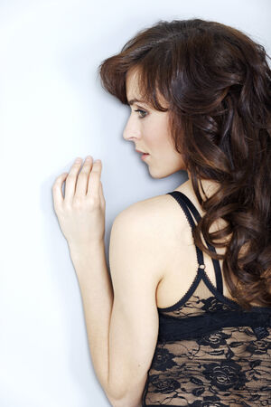 facing a wall: Attractive young woman facing a wall with her hands above her head