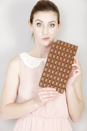 guilty pleasures: Attractive young woman deciding on whether to eat a piece of chocolate.