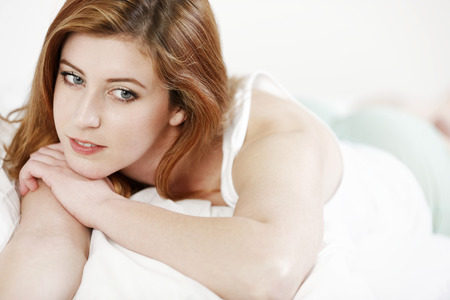 redhaired: Attractive young woman lying on her bed at home relaxing