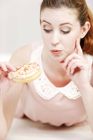 guilty pleasure: Young woman deciding whether to eat an unhealthy doughnut expressing guilt.