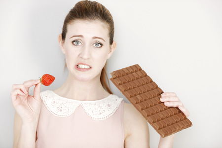 guilty pleasure: Beautiful young woman choosing to eat chocolate or a fresh strawberry. Stock Photo