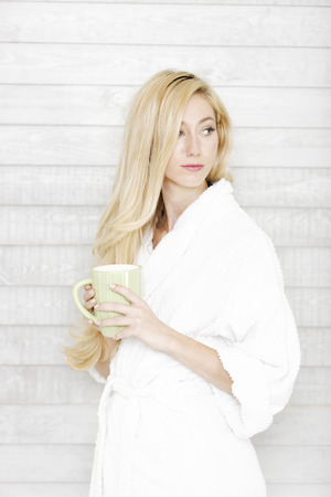 Beautiful young woman in a white robe enjoying a hot drink Stockfoto