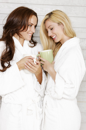 bath robes: Two young friends in white bath robes chatting and drinking