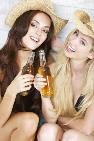 Two friends having fun in bikinis and summer hats photo