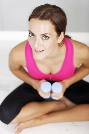 dumb bells: Young woman weight training with dumb bells