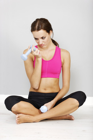 gym girl: Young woman weight training with dumb bells looking bored