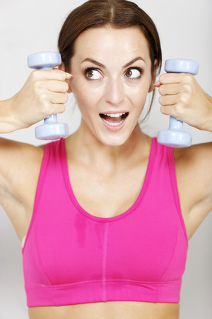 dumb: Young woman weight training with dumb bells