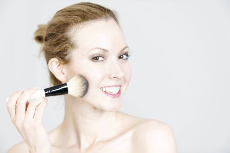 blusher: Attractive young woman applying blusher to her face smiling