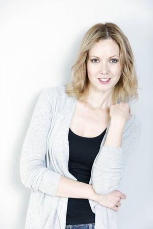 Beautiful young woman wearing a casual cardigan smiling