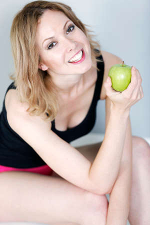Beautiful young woman enjoying a fresh healthy apple smiling photo