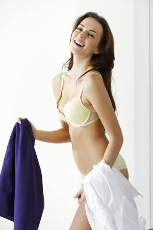 deciding: Attractive young woman getting ready deciding on what clothes to wear. Stock Photo
