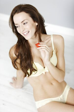 getting dressed: Attractive young woman enjoying a fresh strawberry in her underwear while getting dressed