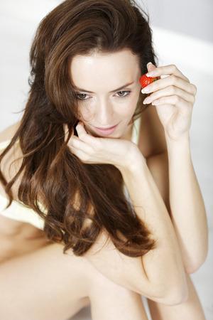 vistiendose: Atractiva mujer joven disfrutar de una fresa fresca en su ropa interior mientras se viste