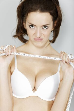 gained: Beautiful young woman unhappy with her waistline measurements.