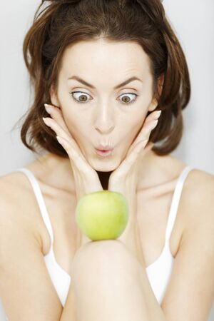 women face stare: Attractive young woman in white underwear with a fresh apple