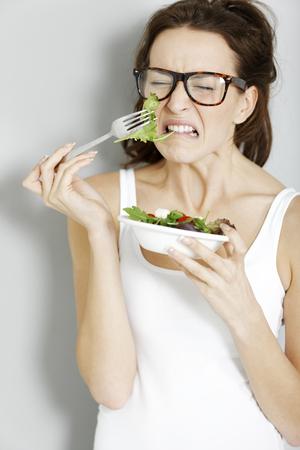 Young woman not enjoying her fresh salad