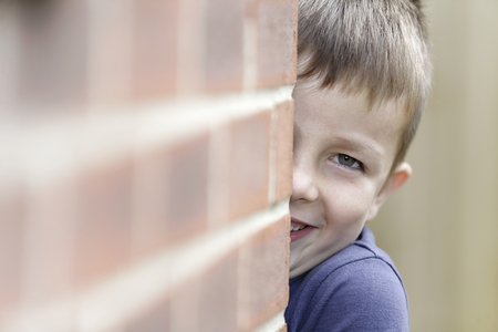 hide and seek: Young boy smiling playing hide and seek