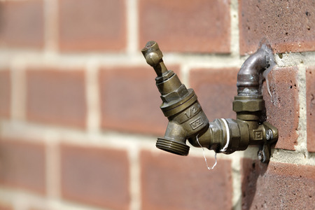 Outdoor tap on a brick wall in the sunshine Stock Photo