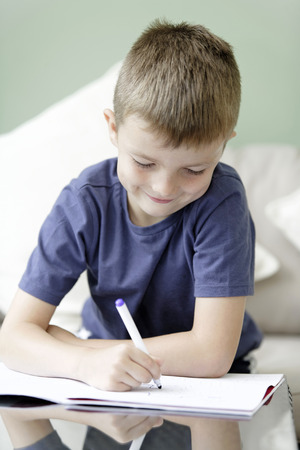 drawing pad: Young boy drawing and writing on a pad doing his homework