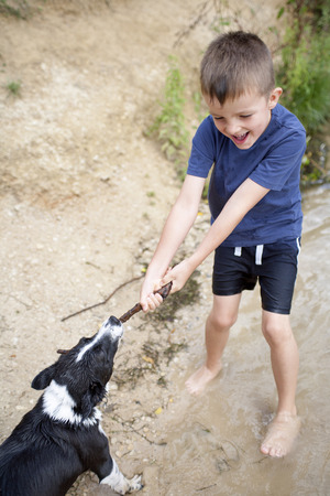 Young boy playing with his dog at the river with a stick photo