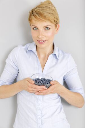 Beautiful young woman in a casual shirt enjoying fresh Blueberries at home