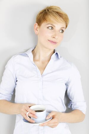 Young woman in casual shirt taking a break and enjoying a fresh cup of coffee