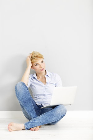 Attractive young woman using her laptop computer sitting on the floor