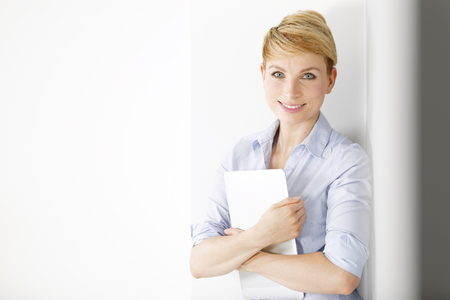 Attractive young woman holding a laptop computer while leaning against a wall.