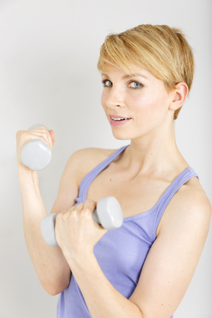 Beautiful young woman exercising with weights at a gym