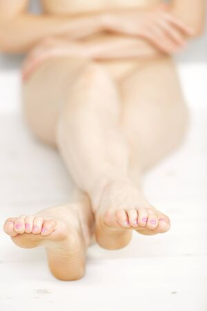 Cropped view of a womans legs and feet on a light wooden floor