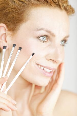 Attractive young woman holding four make up brushes close to her face smiling