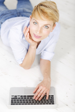 Attractive young woman using her laptop computer lying on the floor Stock Photo