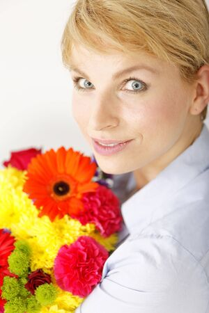 Beautiful young woman smiling and holding a fresh bouquet of colourful flowers while sitting on a wood floor