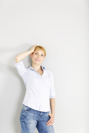 Attractive young woman in a blue casual shirt relaxing in a fashion style pose
