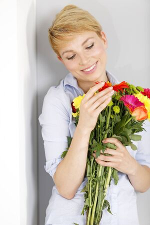 Beautiful young woman smiling and holding a fresh bouquet of colourful flowers
